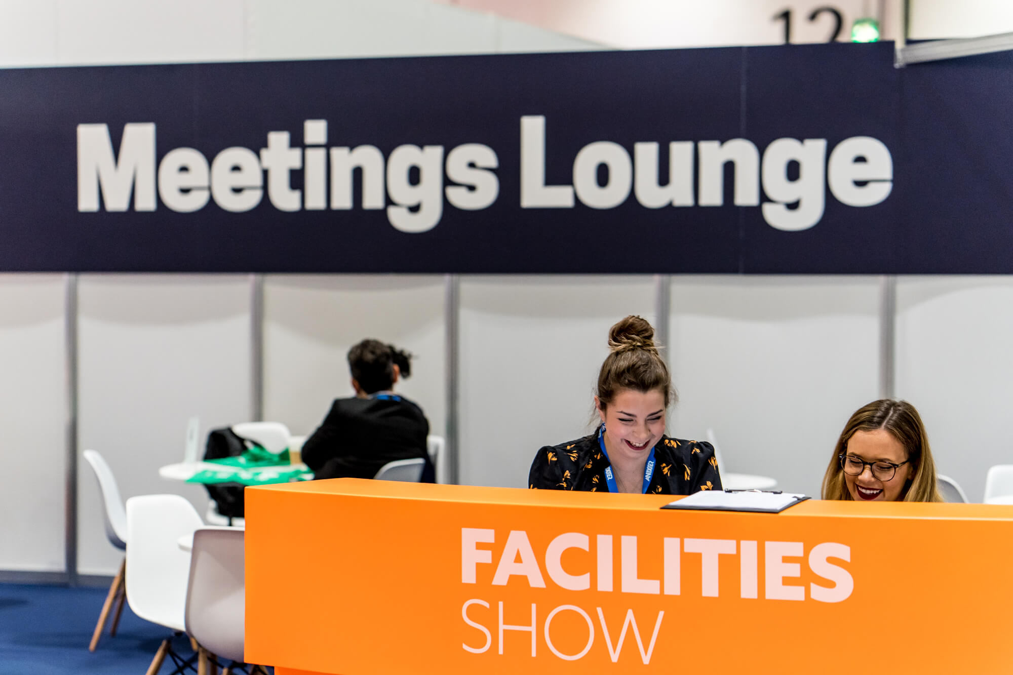 Two individuals on the meetings lounge desk at Facilties Show 2019